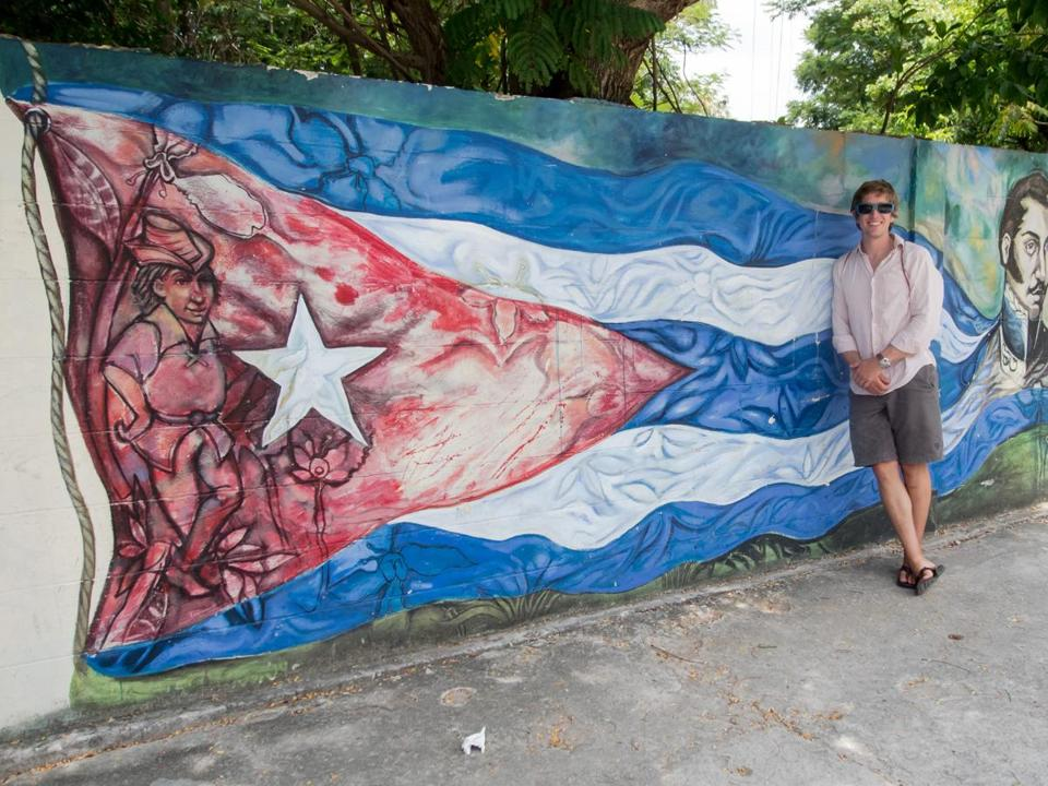 The author in Cuba against a wall of detailed street art.