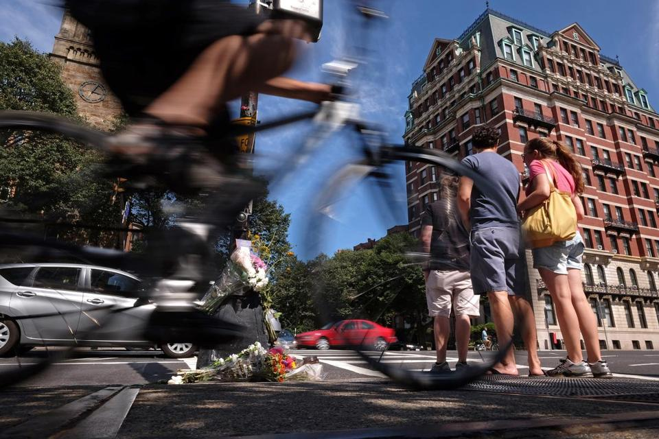 In 2015, bouquets of flowers adorned a light post at the intersection of Massachusetts Avenue and Beacon Street, where a bicyclist was struck and killed.