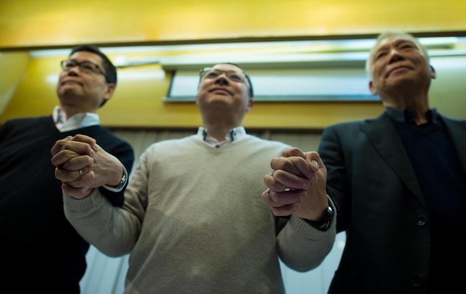 Prodemocracy activists and cofounders of the Occupy movement in Hong Kong (from left) Kin-man Chan, Benny Tai, and the Rev. Yiu-ming Chu, showed their unity after announcing on Dec. 2, 2014, that they would turn themselves into police. Tai, an associate law professor at the University of Hong Kong, has had professional problems since the protest that shut down parts of the city and angered China's government.