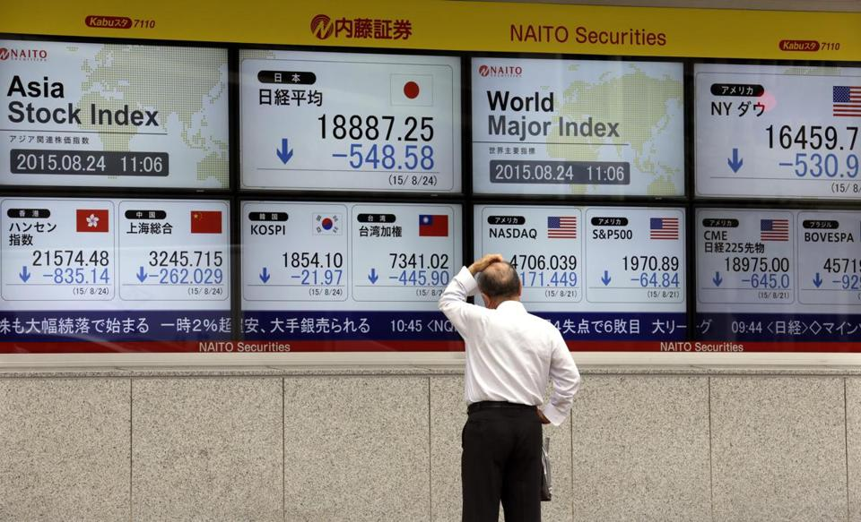 A pedestrian looked at electric boards displaying Tokyo's Nikkei Stock Average on Monday.