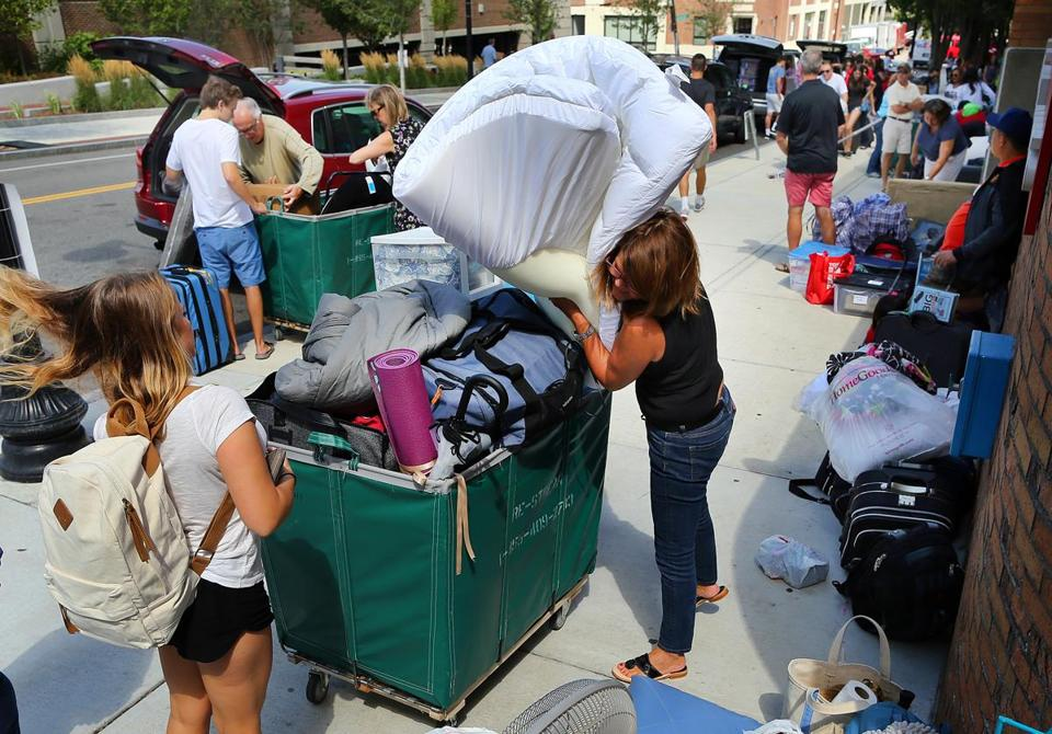 Boston University students, with the help of friends and family, filled large laundry hampers with belongings as they moved into their dorm rooms.
