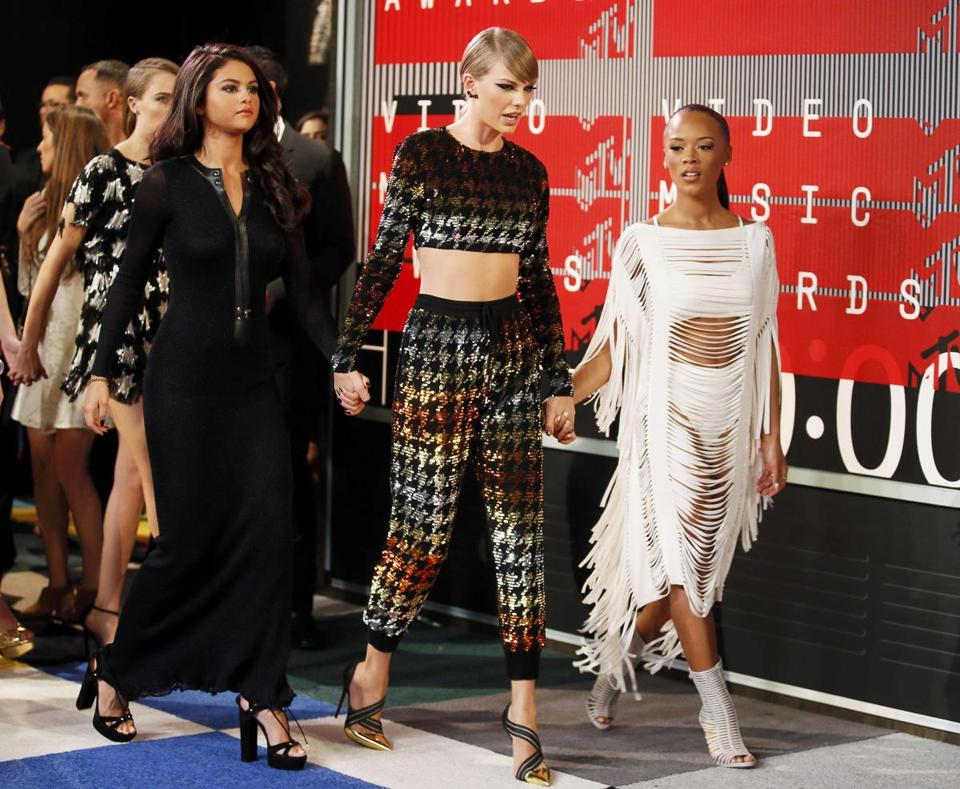 From left: Selena Gomez, Taylor Swift, and actress Serayah McNeill on the MTV Video Awards red carpet.
