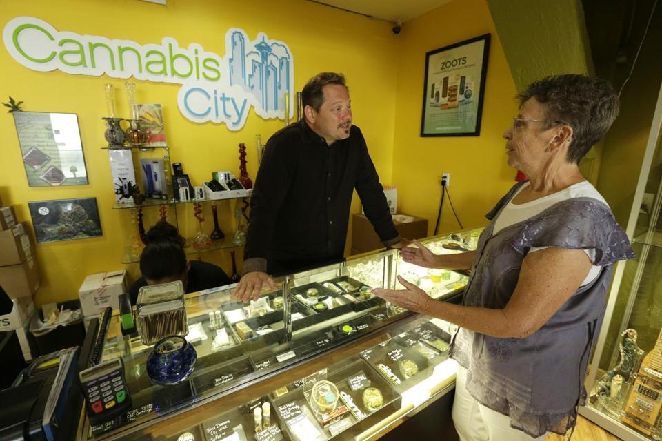 Colorado and Washington have implemented marijuana initiatives similar to the one proposed on the November 2016 ballot. Pictured: James Lathrop (left), owner of the Cannabis City recreational marijuana store in Seattle, spoke with a customer.