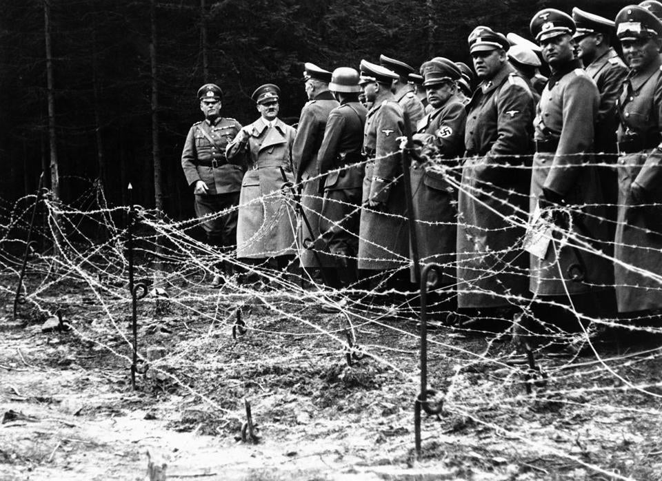 Adolf Hitler (second from left) in front of the barbed wire fortifications at Kreuzbuche, Germany in 1938 after German troops advanced and occupied the second zone of Sudetenland.