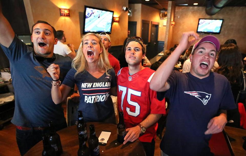 (From left) Dave Pullman, Kristyn Sirois, Chris Faucher, and Patrick Grady take inarecent Patriots game at Stats Bar and Grille in South Boston.