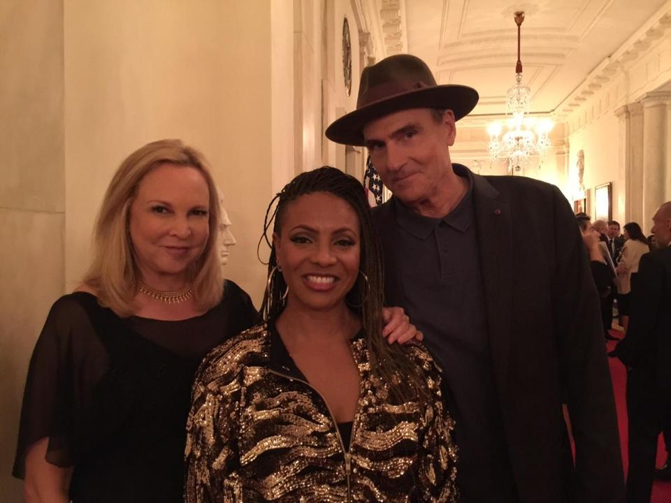 Rapper MC Lyte flanked by Kim and James Taylor at the White House.