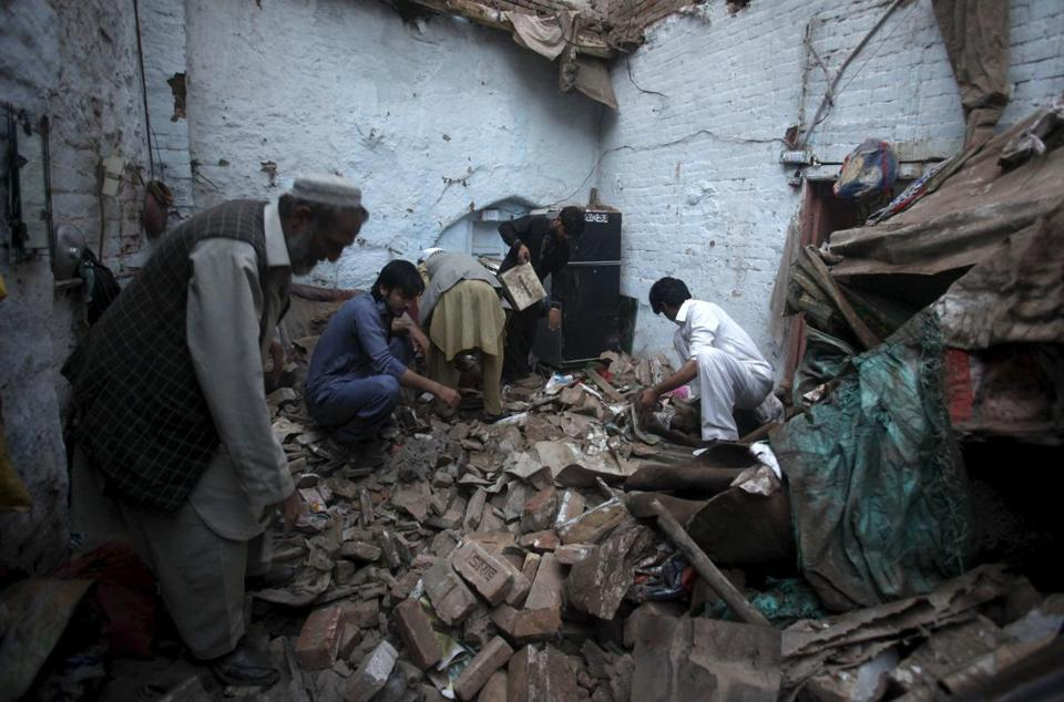 Residents searched for belongings in the rubble of a house after an earthquake in Peshawar, Pakistan, Monday.