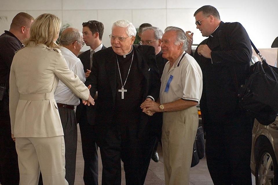 Cardinal Bernard Law (center) was greeted on his arrival to the Fairmont Hotel in 2002.
