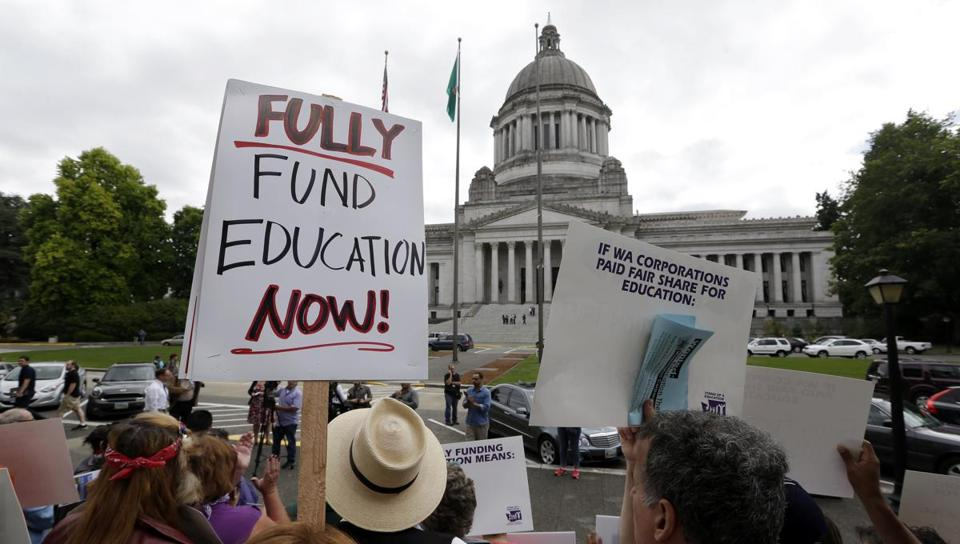A small group of demonstrators stand on the steps of the Temple of Justice and in view of the Legislative Building as they advocate for more state spending on education prior to a hearing before the state Supreme Court Wednesday, Sept. 3, 2014, in Olympia, Wash. The court ordered lawmakers to explain why they haven't followed its orders to fix the way Washington pays for public education. Lawmakers, the governor and others say the court needs to be patient and give the Legislature more time to fulfill the orders from the 2012 McCleary decision. (AP Photo/Elaine Thompson)