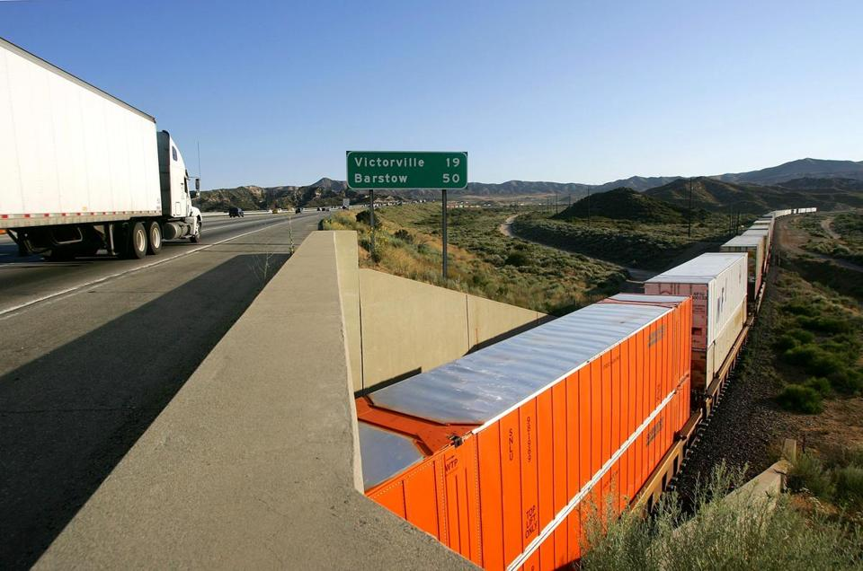 A truck on California's Interstate 15 passed a freight train carrying shipping containers near San Bernardino. The railway is one of the busiest in the nation, transporting goods to and from the ports of Los Angeles and Long Beach.