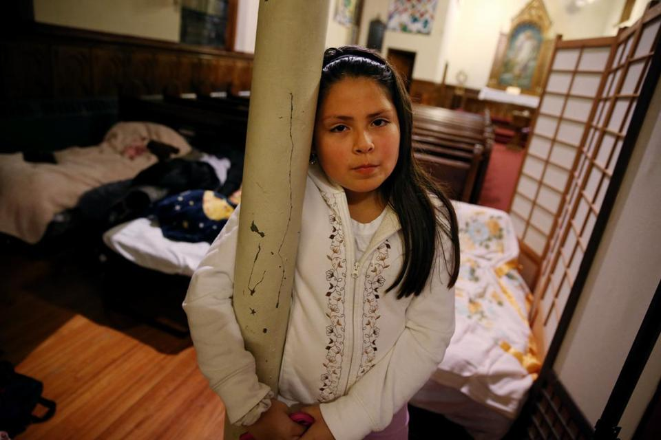 Gabriella Bonilla , 10, posed for a portrait in her family's sleeping area at Our Saviour's Lutheran Church in East Boston.