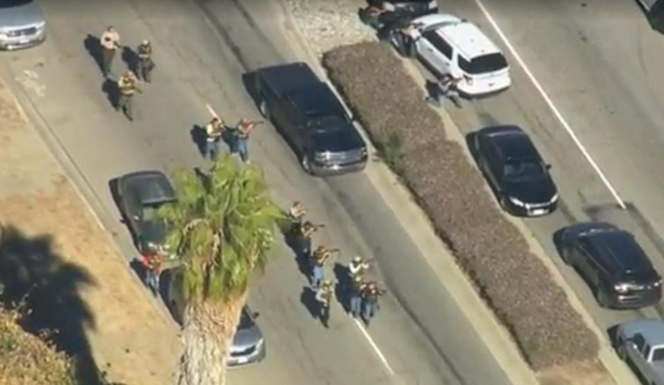 Law enforcement officials walked with weapons drawn outside a social services center in San Bernardino, Calif., as they responded to reports of a shooting Wednesday. Officials later said at least 14 people were killed.