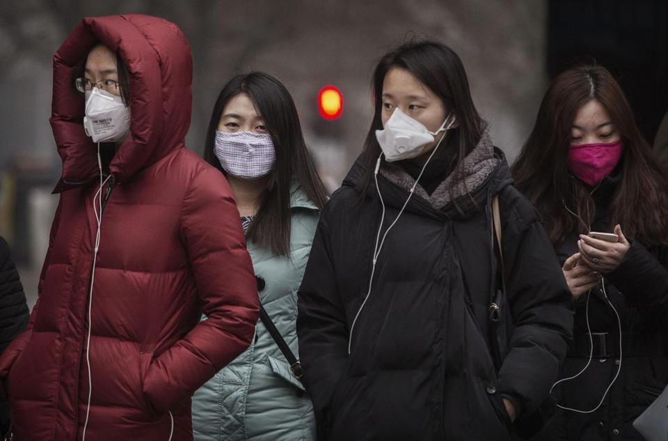 As officials meet in Paris to negotiate international solutions for climate change, several American policy luminaries are urging a carbon tax. Pictured: Women in Beijing wore masks to protect themselves against pollution as they waited to cross a street.
