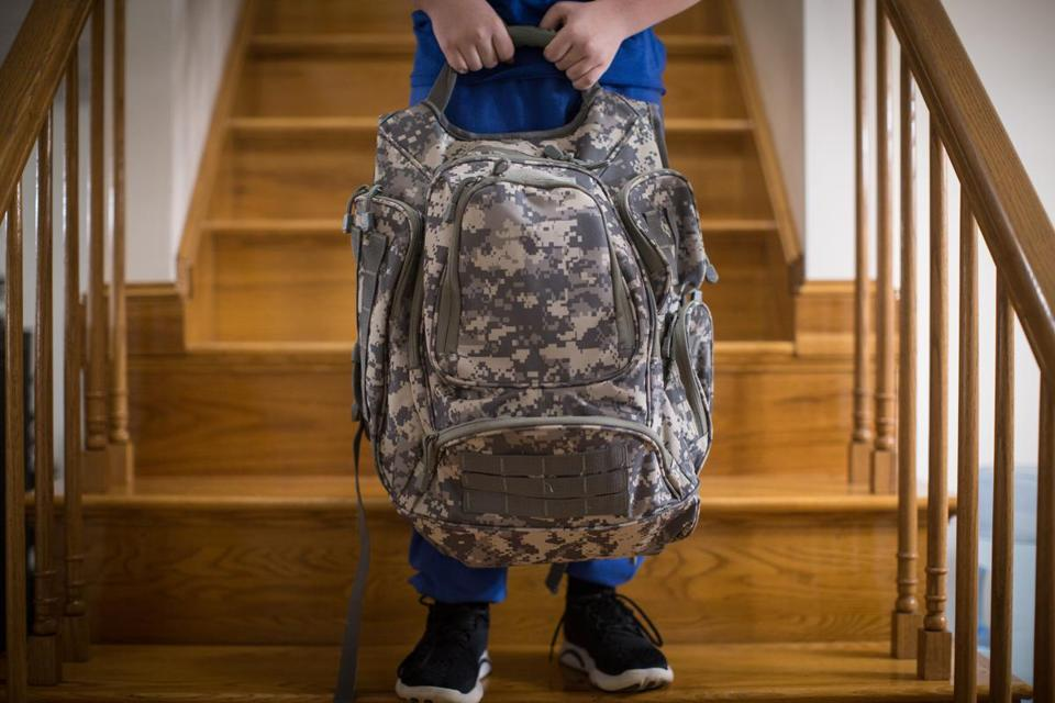 Nicholas Abreau posed for a portrait with the bullet resistant backpack his father Charles bought him in their home in Lowell, MA.