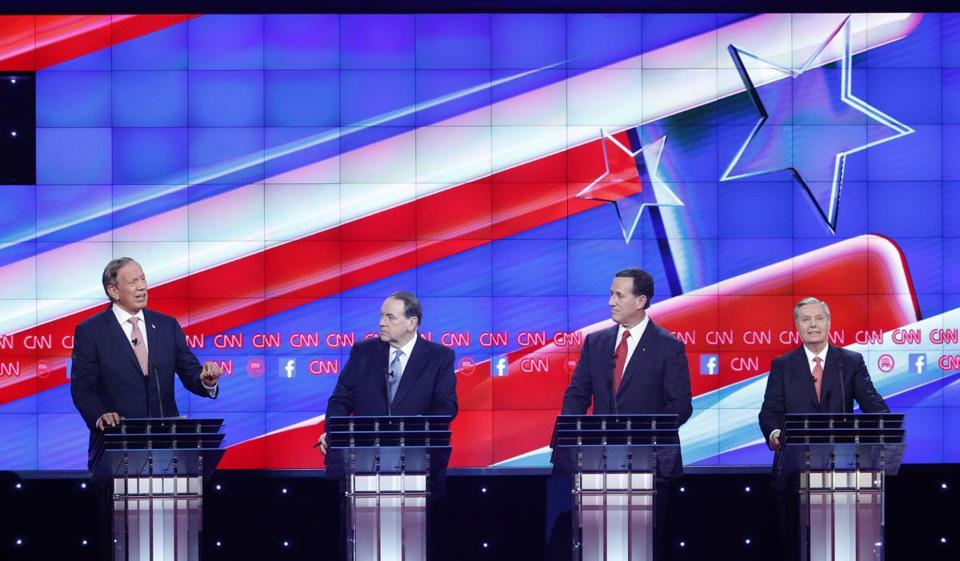 George Pataki, left, spoke as Mike Huckabee, second from left, Rick Santorum, second from right, and Lindsey Graham looked on during the CNN Republican presidential debate.