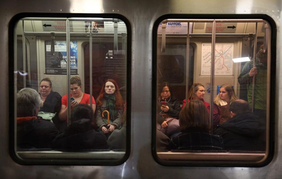 Commuters sit on a Red Line train at the Park Street T Station.