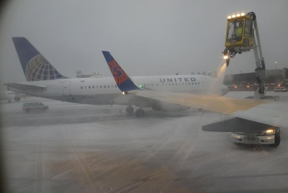 A Sun Country Airlines plane's wing is de-iced as a United Airlines plane waited at the de-icing station during a snowstorm at Logan International Airport in Boston in 2015.