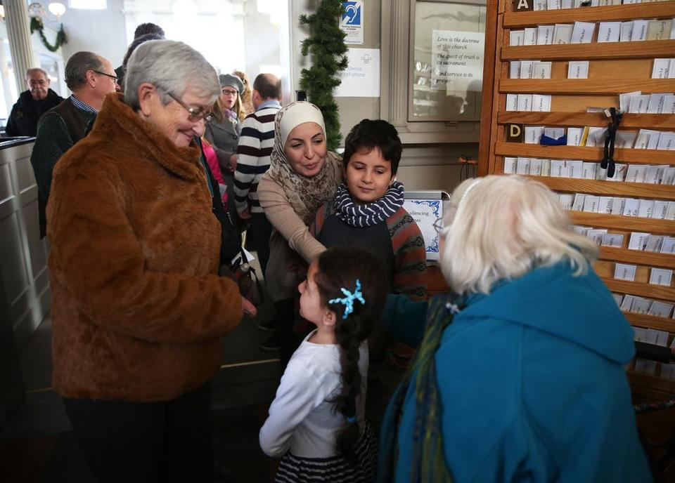Newburyport, MA--1/3/2016--Syrian refugee Amira Elamri (cq), center, and her family are greeted after she addressed the congregation of the First Religious Society Unitarian Universalist, in Newburyport, on Sunday, January 3, 2016. Marjorie Peterson (cq), left, and Niki Rosen (cq), right, talk to her and her son Danny Aldehneh (cq), 9, and daughter Tia Aldehneh (cq), 6. Her husband, Bassel Aldehneh (cq), (stripes) is in the background. Photo by Pat Greenhouse/Globe Staff Topic: 04syrianlocal Reporter: Astead Herndon