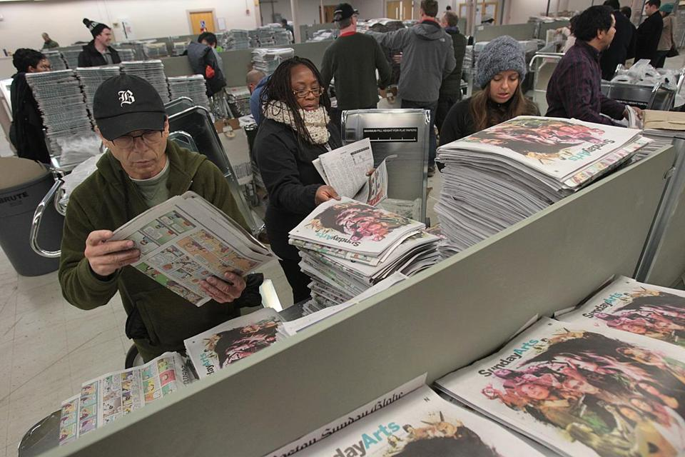 Newton, MA., 01/03/16, Left to right, Boston Globe reporters Michael Rezendes, Meghan Irons, Laura Crimaldi assemble newspapers for delivery. Boston Globe journalists, reporters, editors, photographers, designers, their spouses, fiancee, and children, help assemble the print edition of The Boston Sunday Globe because the new delivery system was having some problems. Globe staff/Suzanne Kreiter