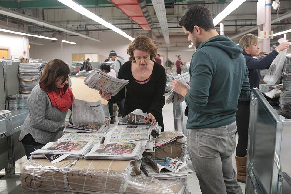 Reporter Katie Johnston (center) assembled newspapers for delivery.