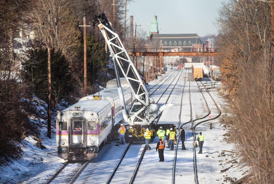 Workers used a specialized crane to get a derailed commuter rail train car back on the tracks Tuesday morning.