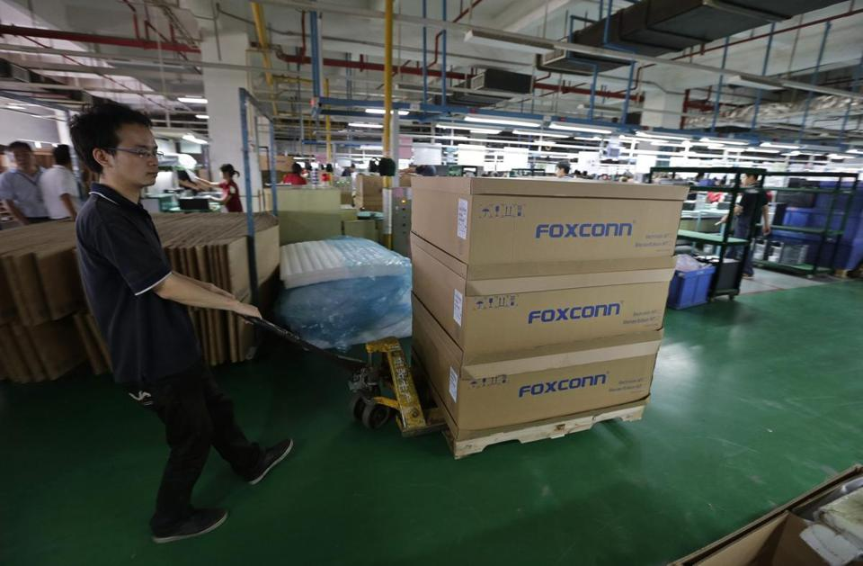 A man pushed a cart inside a Foxconn factory in China. Foxconn is the assembler of most of Apple's latest iPhones.