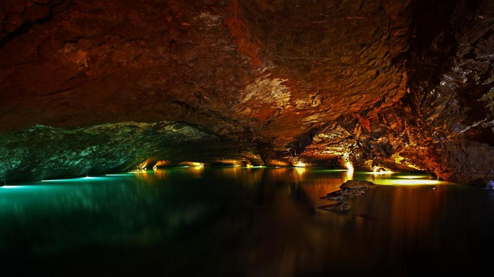 The cavern walls of the Lost Sea glow with subtle lighting. The underground lake attracts more than 150,000 tourists a year.
