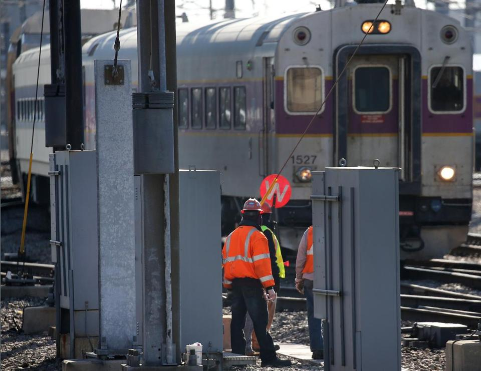 A workman used hand signals for the arrival of a train at South Station Thursday.