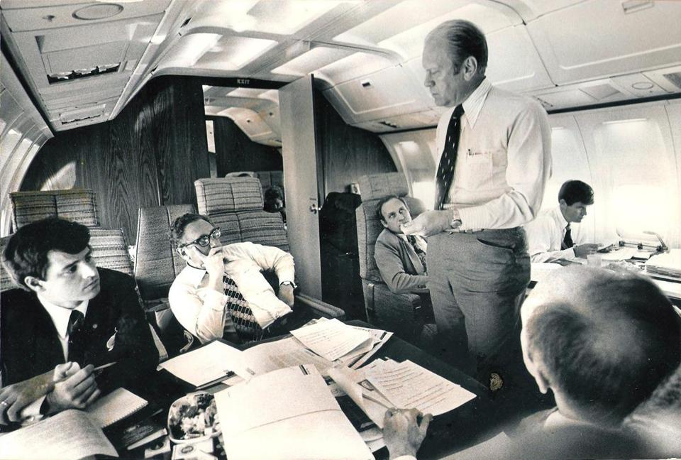 Photo taken aboard Air Force One in 1975. President Gerald Ford is standing at the center, talking to his secretary of state, Henry Kissinger. Seated at Kissinger�s side is Paul Bremer, then Kissinger�s chief aide.Seated at the back, partially obscured by the president, is Dick Cheney.