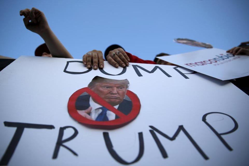 Supporters of Republican U.S. presidential candidate Marco Rubio hold a sign against Republican U.S. presidential candidate Donald Trump during campaign rally in Miami, Florida, March 9, 2016. REUTERS/Carlos Barria