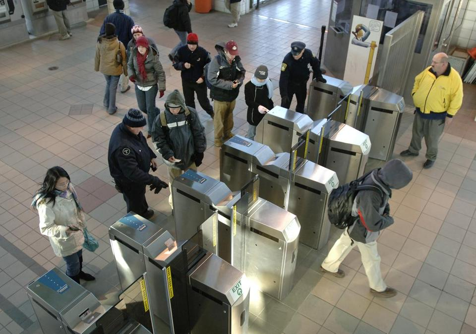 MBTA personnel help BC High students make their way through the fare gates at JFK/UMass station on the Red Line.