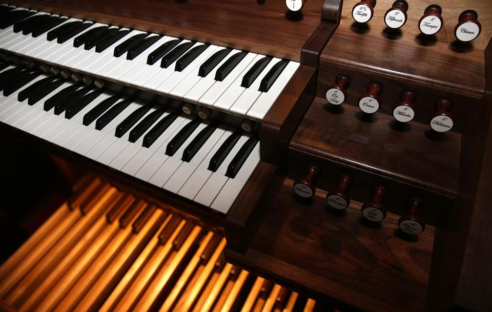 Detail of the console shows the keyboards, stop knobs, and pedalboard of the 1895 organ.