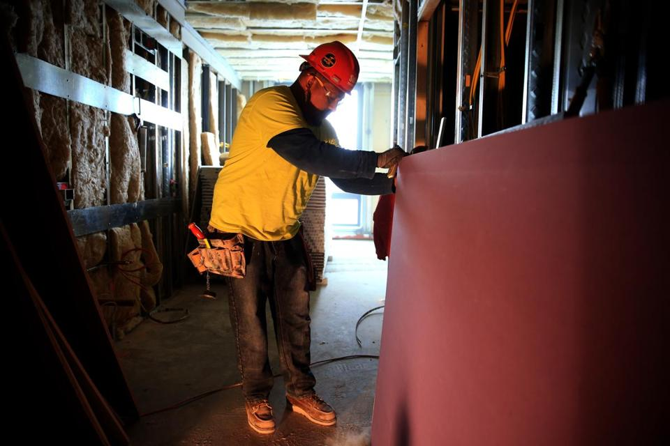 Omar Pedroza installed drywall at an East Boston apartment project. As a job foreman, he said he sometimes had to stuff cash from a subcontractor into his pockets to pay co-workers.