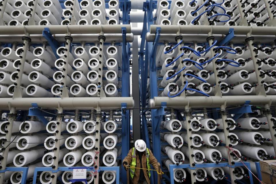 FILE - In this March 11, 2015, file photo, a worker climbs stairs among some of the 2,000 pressure vessels used to convert seawater into fresh water through reverse osmosis in the western hemisphere's largest desalination plant in Carlsbad, Calif. The Carlsbad Desalination Project, scheduled to start operations in late 2015, is expected to provide 50 million gallons of fresh drinking water a day. A plan to pump $1 billion of water spending into drought-stricken California cleared the Legislature on Thursday, March 26, 2015, and was sent to Gov. Jerry Brown, who is expected to sign the legislation. (AP Photo/Gregory Bull, File)