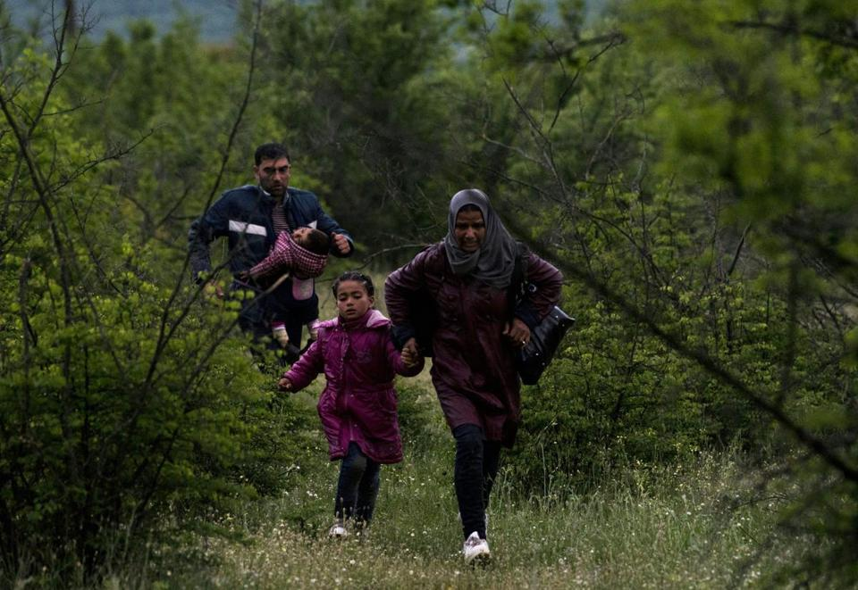 Syrian refugees run in a forest in Macedonia after illegally crossing Greek-Macedonian border near the city of Gevgelija on April 23, 2016. Some 50,000 people, many of them fleeing the war in Syria, have been stranded in Greece since the closure of the migrant route through the Balkans in February. / AFP / JOE KLAMAR (Photo credit should read JOE KLAMAR/AFP/Getty Images)