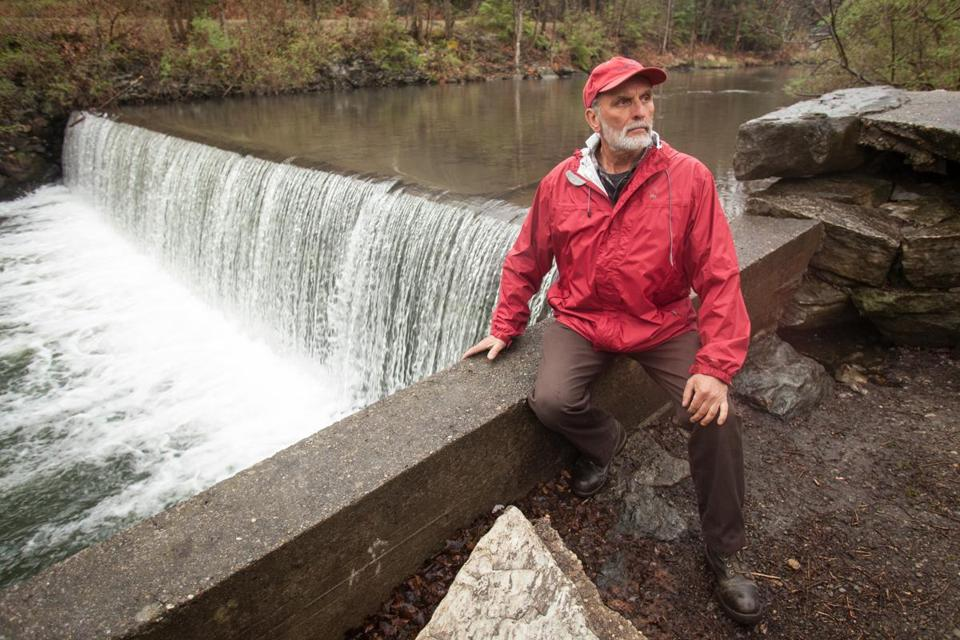 Ken Egnaczak sat on a wall by the small backyard dam that he is trying to get approval to repower.
