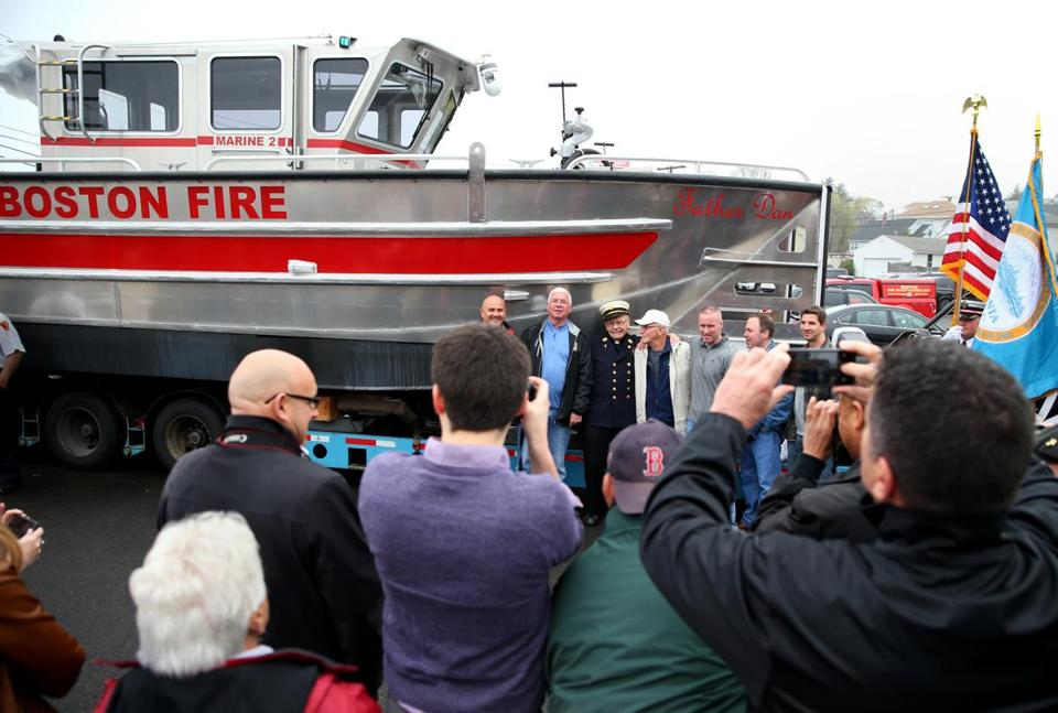 The Rev. Dan Mahoney posed for pictures with the new vessel, which will be used in rescues and to fight fires.