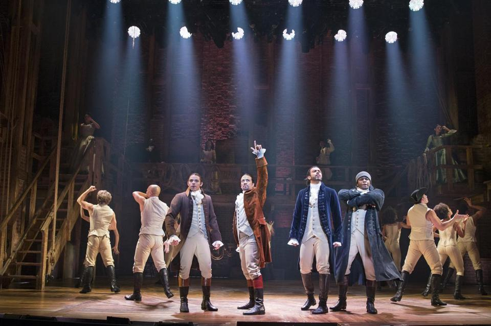 "Lin-Manuel Miranda (raising his arm) and the rest of the Broadway cast of the musical ""Hamilton"" onstage at the Richard Rodgers Theater in New York in 2015."