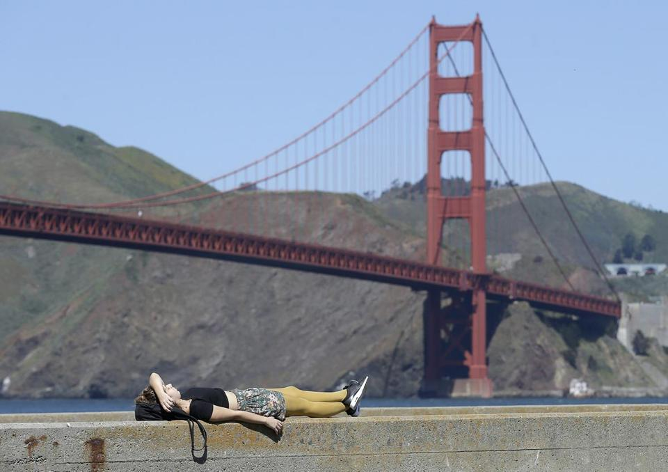 Florencia Guzzetti, visiting from Buenos Aires, lies down on a pier in front of the Golden Gate Bridge in San Francisco, Wednesday, April 6, 2016. A handful of spring heat records are expected to be broken on Wednesday but then temperatures will fall and the weekend is forecast to be wet. (AP Photo/Jeff Chiu)