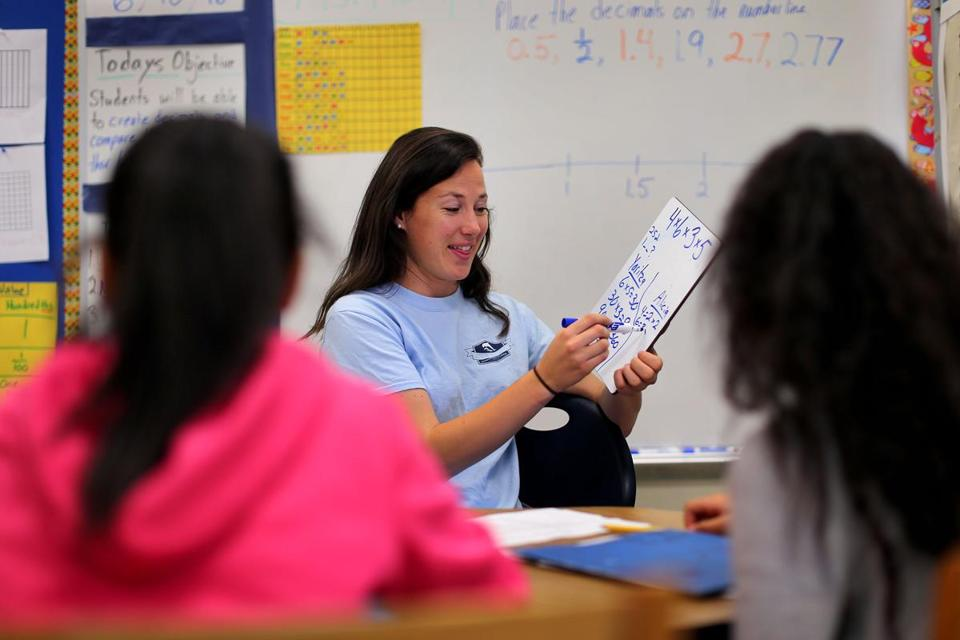 A fifth-grade instructor goes over an equation during math class at Dever Elementary School in Boston.