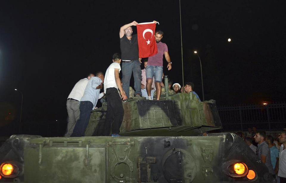 People stood on a tank, holding a Turkish flag after they stopped it in Istanbul, early Saturday.