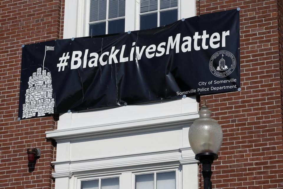 "A ""Black Lives Matter"" banner hangs over the main entrance of City Hall Thursday, July 21, 2016, in Somerville, Mass. Somerville's mayor denied a request from police officers that the banner, which has hung for nearly a year, be removed and replaced with one that says ""All Lives Matter."" (AP Photo/Steven Senne)"