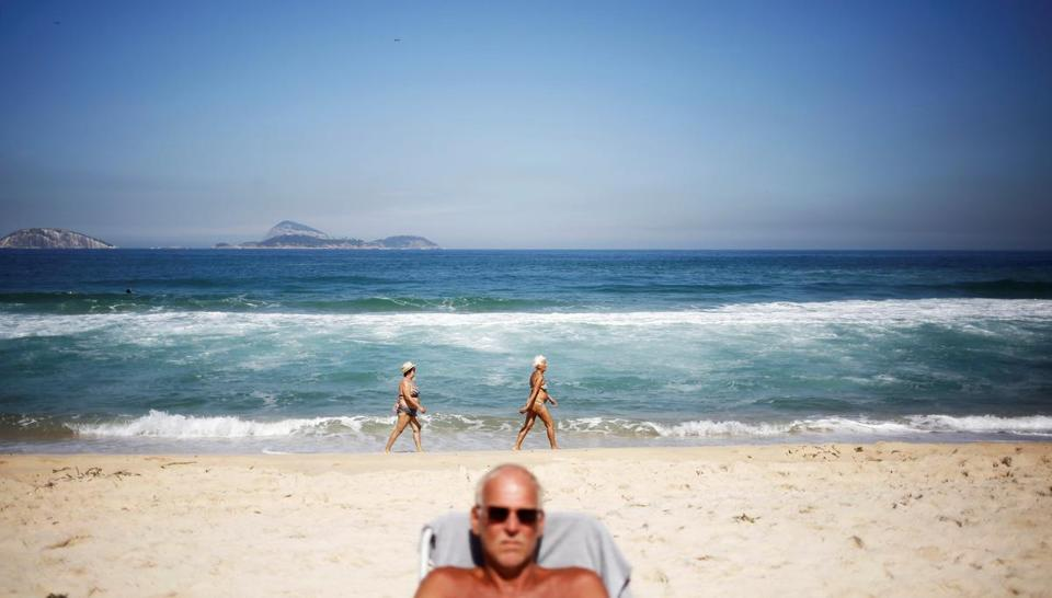 Above: Beachgoers catch some sun at Impanema. Left: Visitors take photos in front of a set of Olympic rings at Copacabana Beach.