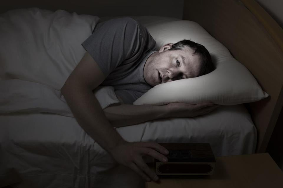 082116sleepdeprivation - Mature man, eyes wide open with hand on alarm clock, cannot sleep at night from insomnia. (iStock/Getty Images)