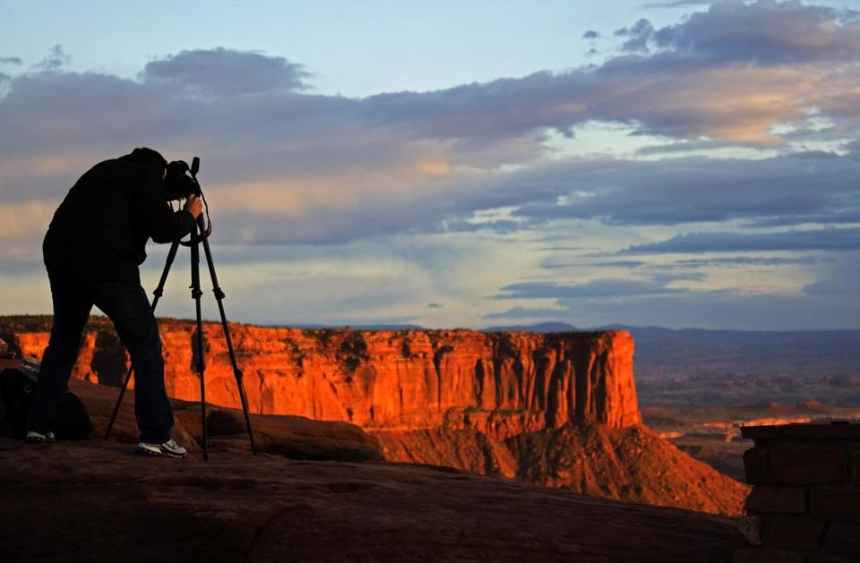 A photographer stood behind a camera at the Green River Overlook at dusk.