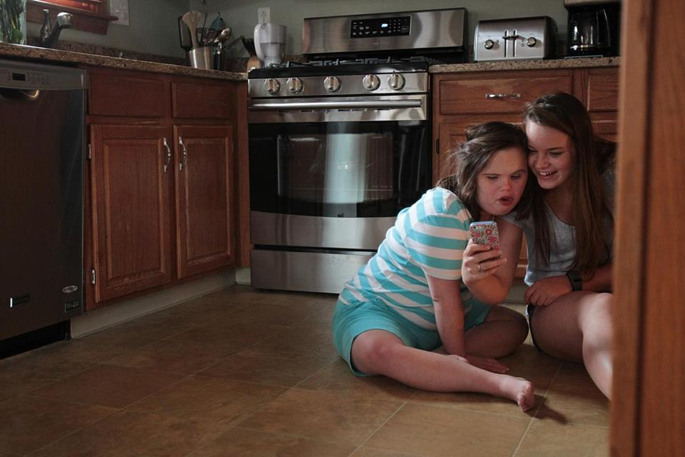 Billerica, MA., 08/16/16, Jessica Doherty, left, takes selfies with one of her personal care assistant----Katelyn Sanderson, cq, in the kitchen of her home. The story follows Jessica Doherty, a girl with autism and down syndrome to see what it's like for her---and other children and young adults with complex physical, intellectual, and emotional needs---when there is no summer programs available to them when school is out of session. Suzanne Kreiter\Globe staff