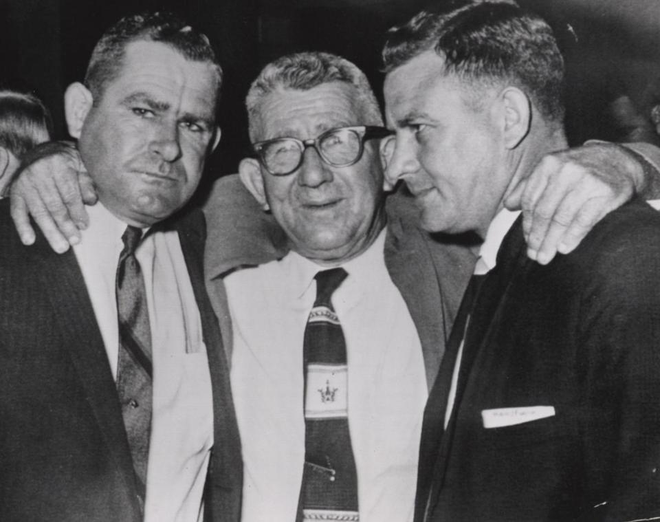 "Defendants William Hoggle (left) and Namon ""Duck"" Hoggle (right) with their father after their acquittal."