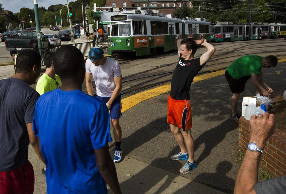 A group of runners who race against the Green Line trains stretched before taking off along Commonwealth Avenue.