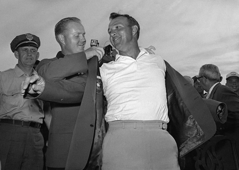 Arnold Palmer slipped into his green jacket with help from Jack Nicklaus after winning the 1964 Masters.