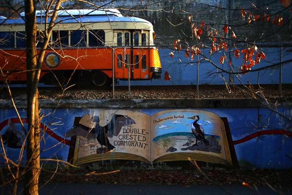 Boston, MA - 03/08/16 - A trolley passes a mural on the Neponset River Greenway, which runs alongside much of the route of the Mattapan Ashmont High Speed Trolley Line. Numerous murals adorn the way. Lane Turner/Globe Staff Section: MAG Reporter: in caps Slug: